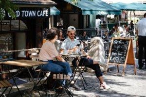 Jeunes hommes dans une terrasse de restaurant en terrasse utilisant laissant un pourboire en ligne sur son smartphone
