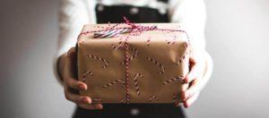 Une personne tend vers nous un cadeau de Noël symbolisant le reconfinement.
